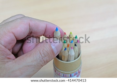 Big hand pick up small blue color pencil  - stock photo