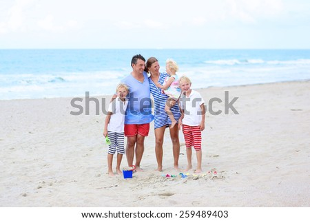Big happy family of five - young active parents with three kids, twin teenager sons and cute toddler daughter - enjoying summer vacation together building sand castles on the beach at the sea - stock photo