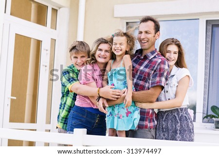 Big happy family stands beside their house - stock photo