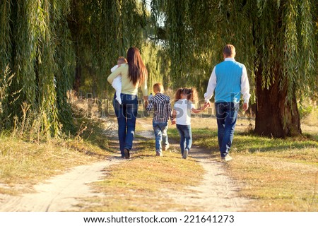 Big happy family walking on the road in the park. Father, mother, son, daughter and baby holding hands and going together. Rear view. Family Ties concept. - stock photo
