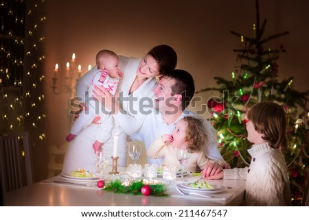 Big happy young family with three children enjoying Christmas dinner celebration, parents and kids - teen age boy, little toddler girl and baby in a dark dining room with candles and Xmas tree - stock photo