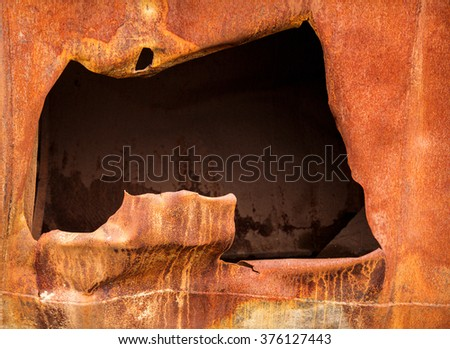 big hole in a rusty steel plate - stock photo
