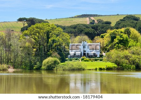 Big house next to lake and hills. Shot in Kuils River Winelands, near Stellenbosch/Cape Town, Western Cape, South Africa. - stock photo