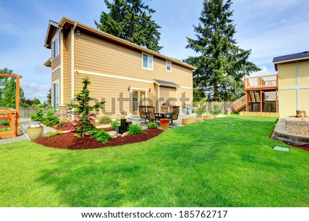 Big house with backyard patio area and beautifully designed flower bed - stock photo