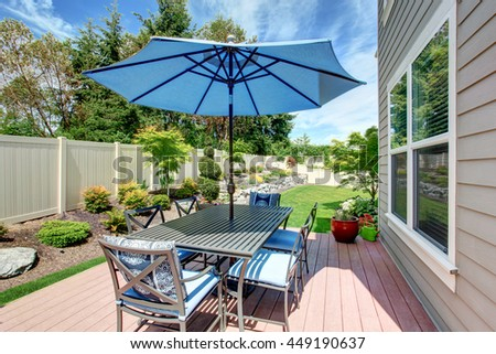 Big house with backyard patio with table set and landscape design - stock photo