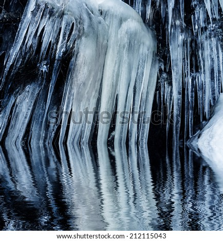 big icicles on a rock - winter time - stock photo