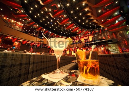big illuminated hall. coaches and tables. wineglass and glass with drinks in center of image. focus on top of wineglass. people in out of focus. wide angle. - stock photo