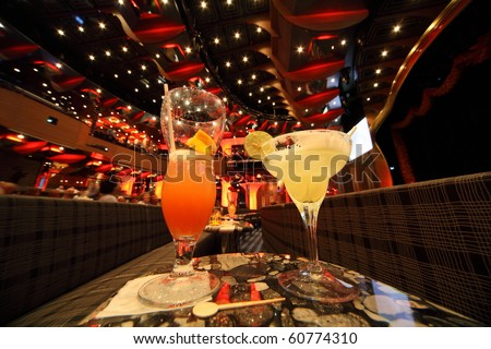 big illuminated hall. coaches and tables. wineglass and glass with drinks in center of image. focus on top of glass. wide angle. - stock photo