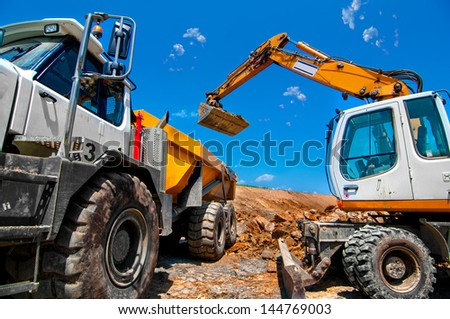 Big, industrial excavator on new construction site loading a dumper truck, in the background the blue sky and sun - stock photo