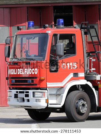 big Italian fire trucks with lettering and blue sirens - stock photo