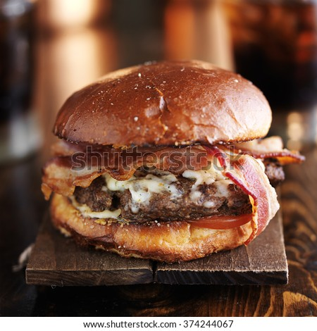 big juicy burger with bacon and melted pepper jack cheese - stock photo