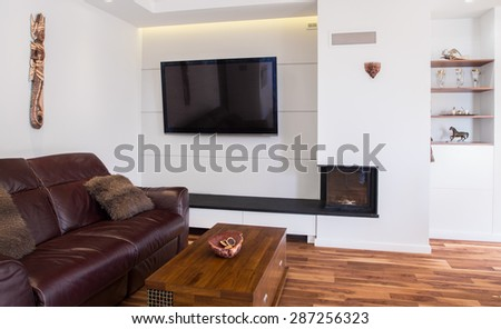 Big leather couch in lounge with wooden parquet - stock photo