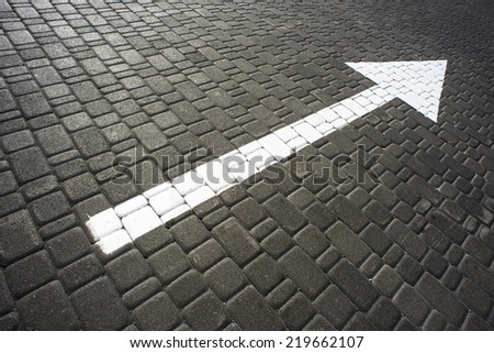 Big long white arrow on the road - stock photo