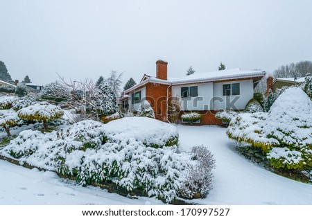 Big luxury house in snowfall cold, chilly and frosty winter time, covered with snow. Vancouver, Canada. - stock photo