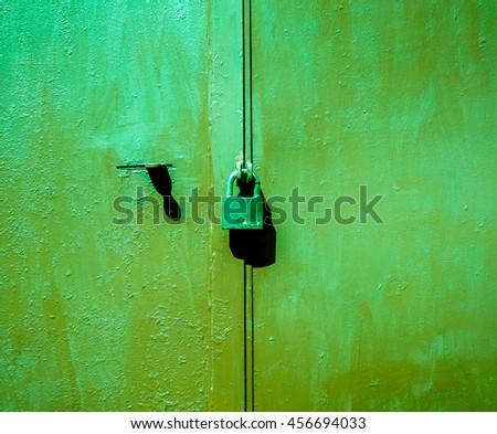 Big metal door with rusty cracked paint and dark lock - stock photo