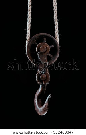 Big metal hook hanging on rope isolated on black background. - stock photo