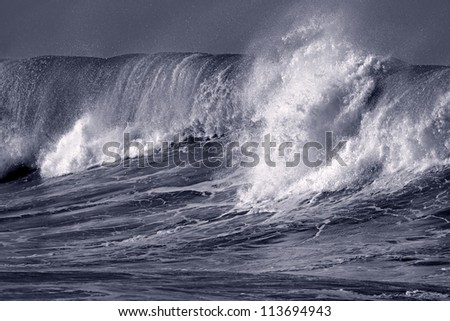 Big ocean wave crashes on to the Portuguese coast - Toned black and white - stock photo