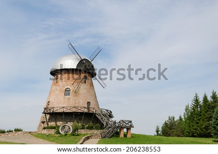 big old retro brick mill with stairs on the summer forest background  - stock photo
