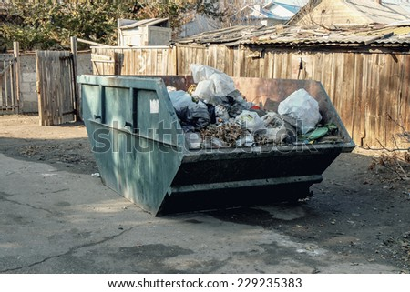 Big overfilled  trash dumpster in ghetto (Astrakhan, Russia) - stock photo