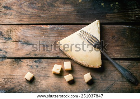 Big piece and little cubes of Belgian cheese with vintage fork over wooden background. Top view. - stock photo