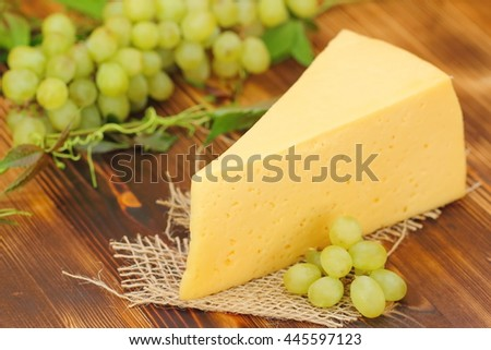 Big piece of cheese and yellow grape - stock photo