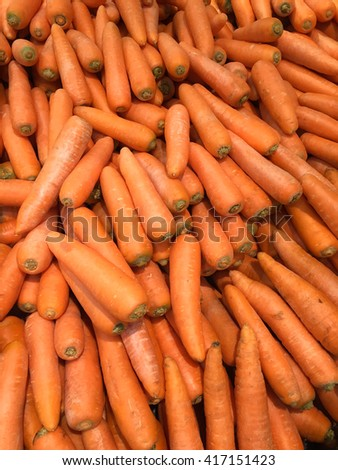 Big pile of fresh carrots in market ready for sale - background - stock photo