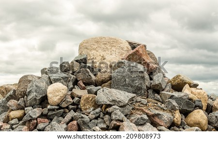 big pile of rocks and boulders piled in a heap under a grey dark cloudy sky in summer time - stock photo