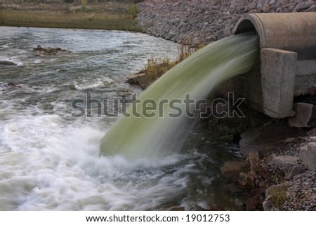 Big pipe under a rock dam supplying water to irrigation reservoir in Colorado. - stock photo
