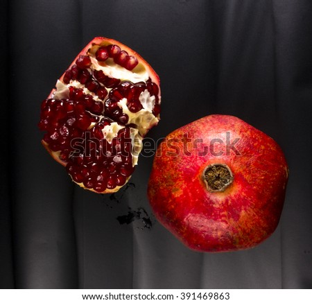 Big Pomegranate fruit and seeds on black background, closeup - stock photo