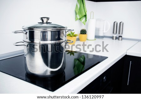 Big pot in modern kitchen with induction stove - stock photo