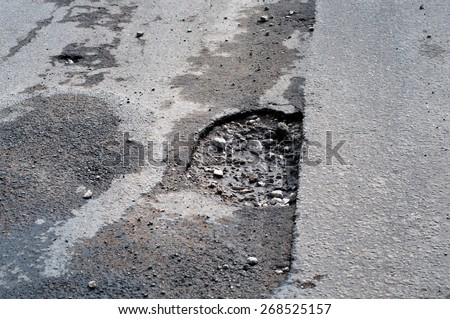 Big pothole in road after spring thaw - stock photo