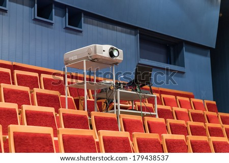 Big projector in hall with red seats - stock photo