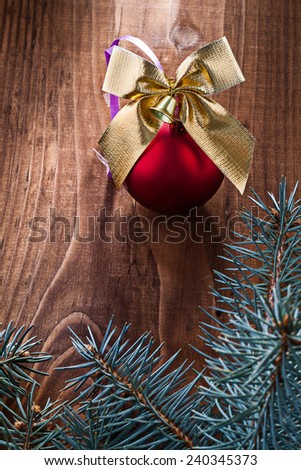 big red christmas ball and gold colored bow with branches of fir tree on old wooden board - stock photo