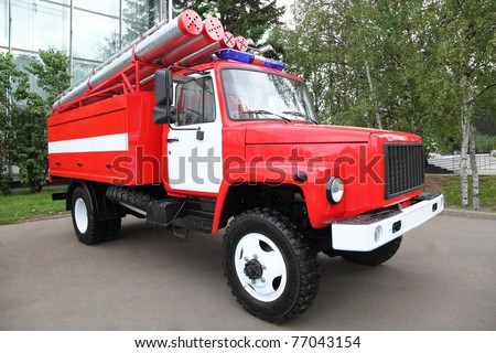 Big red fire engine with pipes and flasher on the roof at summer day - stock photo