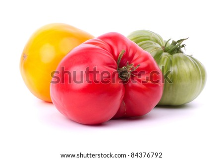 Big red, green and yellow tomatoes on white - stock photo