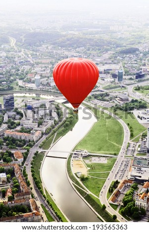 Big red hot air balloon over city and river panorama - stock photo