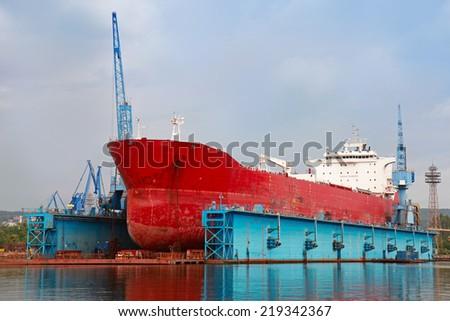 Big red tanker under repairing in blue floating dock, Varna - stock photo