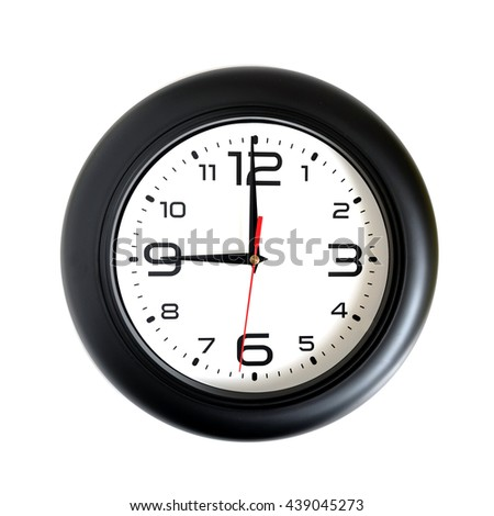 Big round wall clock, with a dark rim on a white background close-up and arrows showing nine o'clock - stock photo