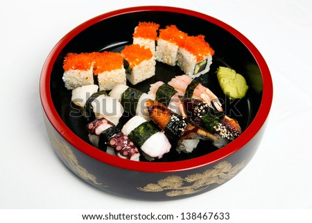Big round white dish with different kind of rolls and sushi isolated over white background. top view. - stock photo