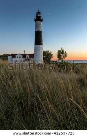 Big Sable Lighthouse - Ludington Michigan - The moon shines over Big Sable Lighthouse along the shores of Lake Michigan at sunset. Dune grasses sway in a gentle breeze - stock photo