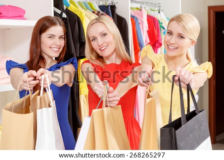 Big sale. Three smiling female shoppers in colorful dresses stretching out paper bags standing new the clothing rack in a fashion store - stock photo