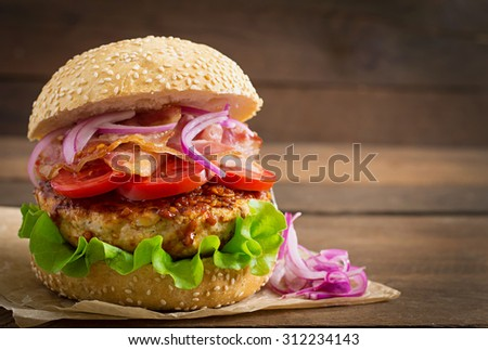 Big sandwich - hamburger burger with beef, red onion, tomato and fried bacon. - stock photo