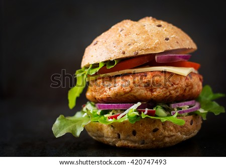 Big sandwich - hamburger with juicy chicken burger, cheese, tomato,  and red onion on black background - stock photo