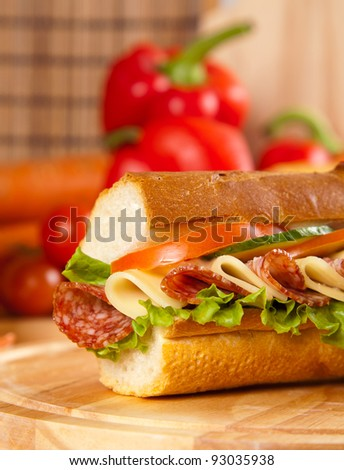 big sandwich with fresh vegetables on wooden board - stock photo