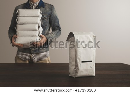 Big sealed hermetic blank labeled package presented in focus in front of unfocused worker man loaded with other packages. Retail, good delivery service - stock photo