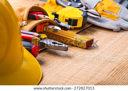 big set of construction tools in toolbelt hardhat screwdriver pencil nippers pliers  wrench tape measure cutter gloves on wooden board  - stock photo