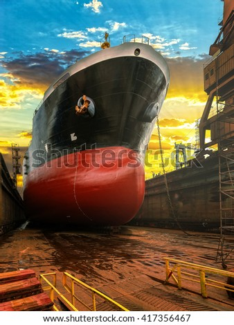 Big ship during repairs on dry dock in shipyard. - stock photo