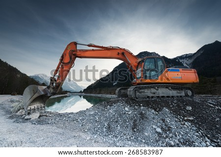 big shovel excavator standing on gravel stones before lake - stock photo