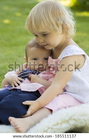 Big sister holding little brother - stock photo
