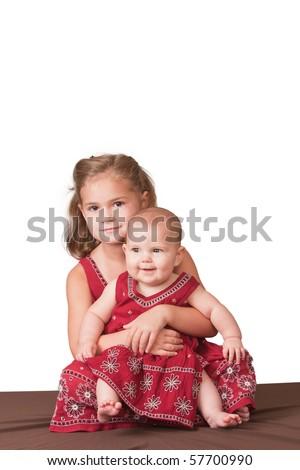 Big sister holding little sister. White background. - stock photo